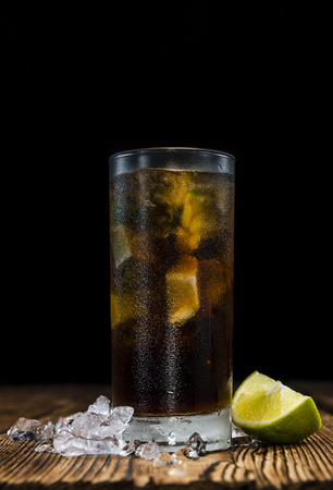 longdrink: Homemade Cuba Libre with fresh lime, brown rum and crushed ice on an old wooden table