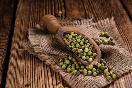 Portion of green Peppercorns (close-up shot) on wooden background