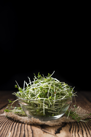 detailed shot: Portion of fresh Garden Cress (detailed close-up shot) on wooden background