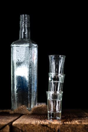 shot glasses: Pile of empty shot glasses (close-up shot) on wooden background Stock Photo