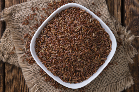 a portion: Portion of red Rice (close-up shot) on wooden background