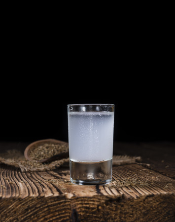 shot glass: Frozen Ouzo in a shot glass (selective focus) on wooden background