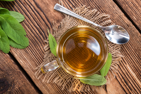 dring: Sage Tea in a small glass on wooden background