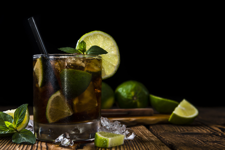 ice crushed: Cuba Libre longdrink with pieces of fresh lime and crushed ice on wooden background