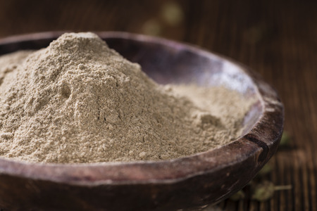 cardamon: Heap of Cardamon Powder (close-up shot) on rustic wooden background