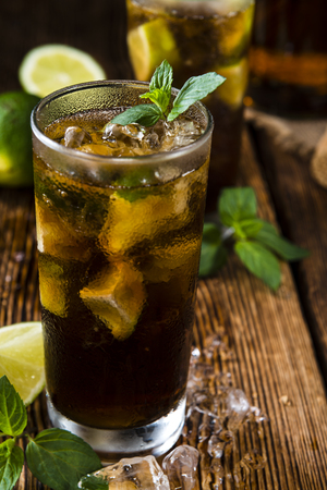 longdrink: Cold Longdrink (Cuba Libre) with brown rum and fresh lime on rustic wooden background Stock Photo