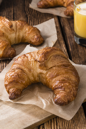traditionally french: Some fresh baked Croissants on rustic wooden background Stock Photo