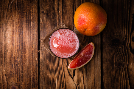 squeezed: Freshly Squeezed Grapefruit Juice (close-up shot) on vintage wooden background
