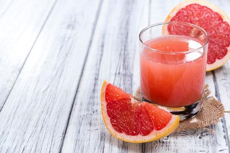 grapefruit juice: Glass with Grapefruit Juice (close-up shot) on wooden background