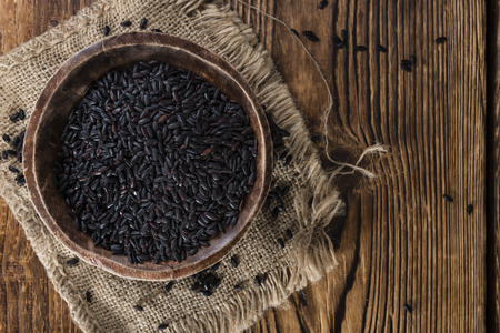 Portion of Black Rice (close-up shot) on wooden background Stock Photo