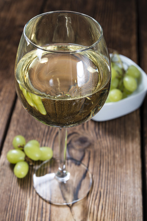 whine: White Whine on an old vintage wooden table