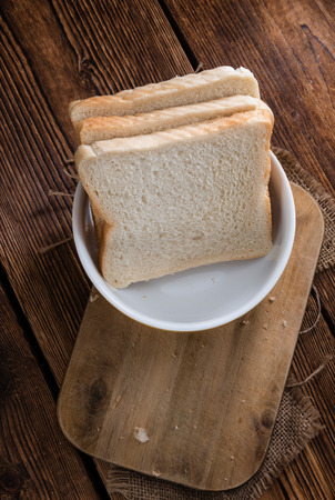a portion: Portion of Toast Bread (selective focus) on wooden background
