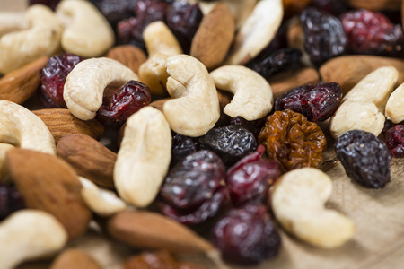 Portion of mixed nuts and fruits (trail mix) on wooden background