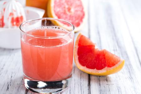 grapefruit juice: Freshly Squeezed Grapefruit Juice (close-up shot) on vintage wooden background