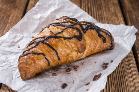 traditionally french: Fresh made Chocolate Croissants (close-up shot) on wooden background Stock Photo