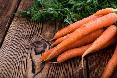Bunch of Carrots (close-up shot) on an old, wooden table