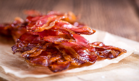 streaky: Portion of fried Bacon (selective focus) on wooden background Stock Photo