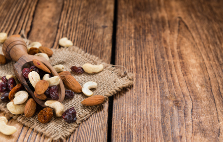 nuts: Trail Mix on wooden background (mixed dried fruits with nuts)