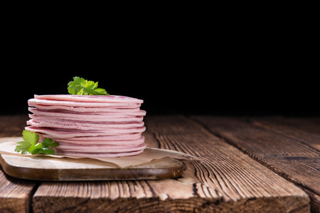 bologna baloney: Old rustic wooden table with Ham Sausage (selective focus)