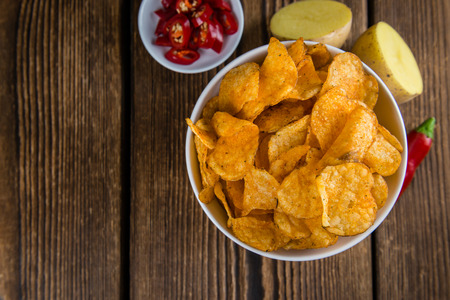 a portion: Portion of chilli Potato Chips (close-up shot) on wooden background Stock Photo
