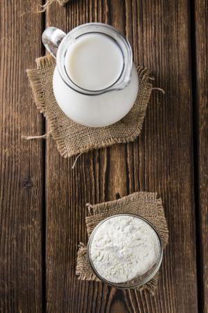 Milchpulver (close-up Schuss) auf einem alten Vintage-Holz-Tisch (selektive Fokus)