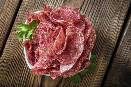 manjar: Rebanadas del salami (enfoque selectivo) en una tabla de madera de la vendimia