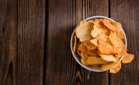 snacking: Rippled Potato Chips (selective focus) on an vintage wooden table