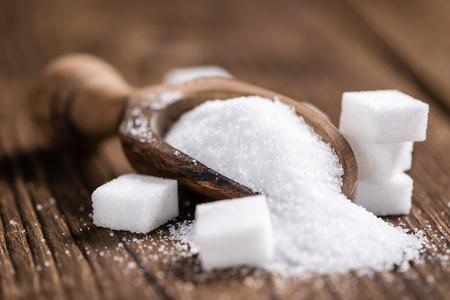 Gedeelte van witte suiker (gedetailleerde close-up shot, selectieve aandacht) op houten achtergrond Stockfoto