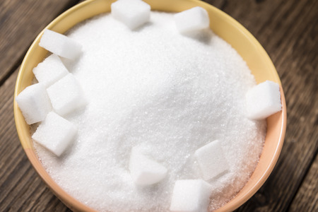 sweeten: Portion of white Sugar (selective focus) in a bowl on vintage wooden background
