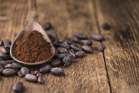 Portion of natural Cocoa powder on an old wooden table (selective focus)