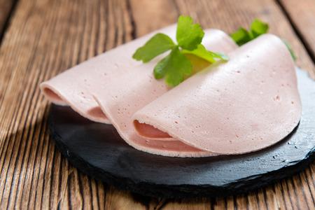 bologna baloney: Mortadella (selective focus) sliced on vintage wooden background (close-up shot)