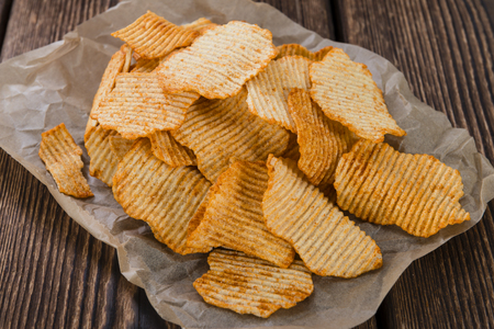a portion: Portion of Potato Chips (rippled, selective focus) on wooden background Stock Photo