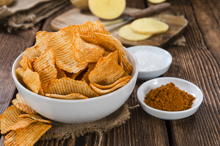 Bowl with rippled Potato Chips (selective focus) on wooden background