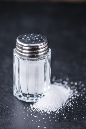 salt shaker: Salt Shaker (close-up shot) on a slate slab (selective focus) Stock Photo