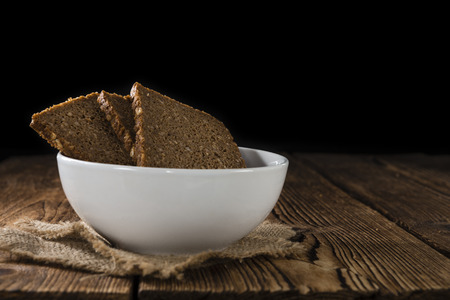 brown bread: Some slices of brown Bread (selective focus) on wooden background Stock Photo