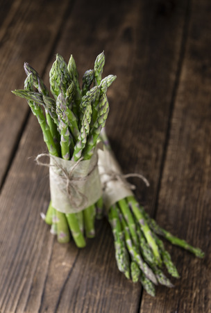 nutritiously: Fresh green Asparagus (selective focus, close-up shot) on wooden background