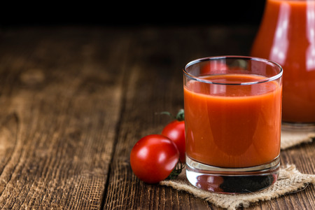 Fresh made Tomato Juice (selective focus) on wooden background