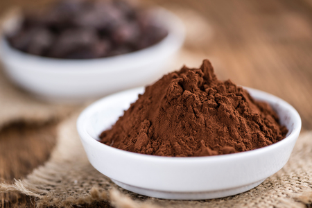 detailed shot: Cocoa powder (selective focus) as detailed close-up shot on wooden background