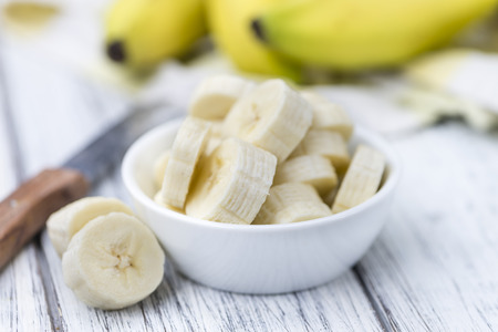 Bananas (chopped) on an old wooden table (selective focus)