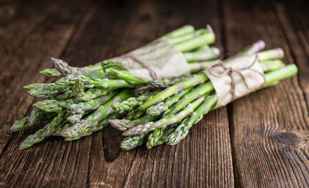 nutritiously: Portion of green Asparagus (close-up shot) on wooden background Stock Photo