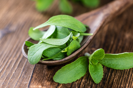 Vintage wooden table with Stevia leaves (selective focus; close-up shot)