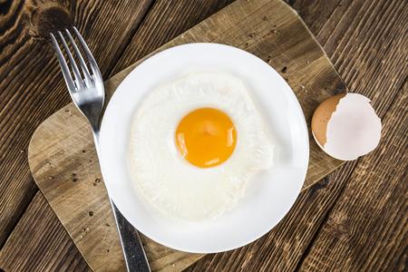 huevos estrellados: Los huevos fritos en el fondo de cosecha de madera (enfoque selectivo, disparo de primer plano)