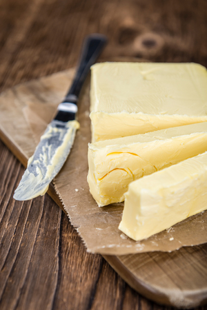 butterfat: Old wooden table with a portion of Butter (selective focus; close-up shot)) Stock Photo