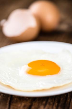 huevos estrellados: Wooden table with Fried Eggs (selective focus; close-up shot)