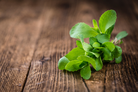 sweetening: Old wooden table with Stevia leaves (selective focus; detailed close-up shot) Stock Photo