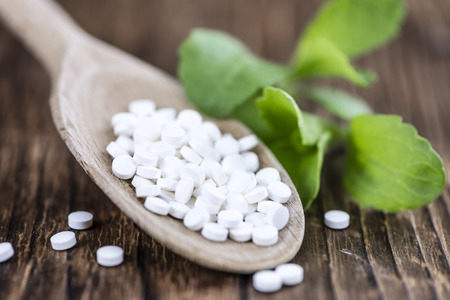 Stevia sweetener pills (selective focus) on wooden background