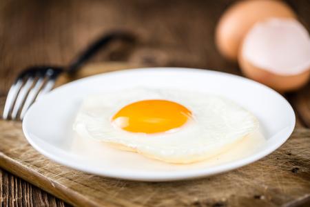huevos estrellados: vieja mesa de madera con huevos fritos (enfoque selectivo, disparo de primer plano) Foto de archivo