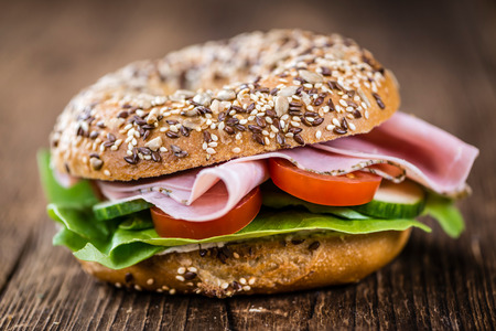 Bagel with Ham (selective focus) on an old woden table (close-up shot) Stock Photo