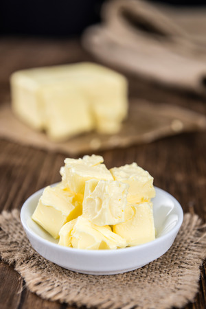 butterfat: Portion of fresh Butter (selective focus; close-up shot) on wooden background