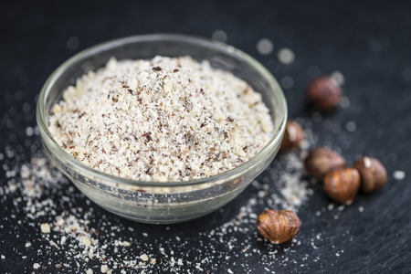grounded: Grounded Hazelnuts (selective focus; close-up shot) on vintage background